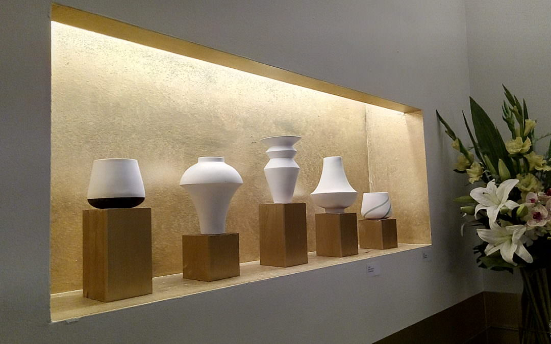 Weisse Vasen in einer goldenen Vitrine neben Blumenbusch