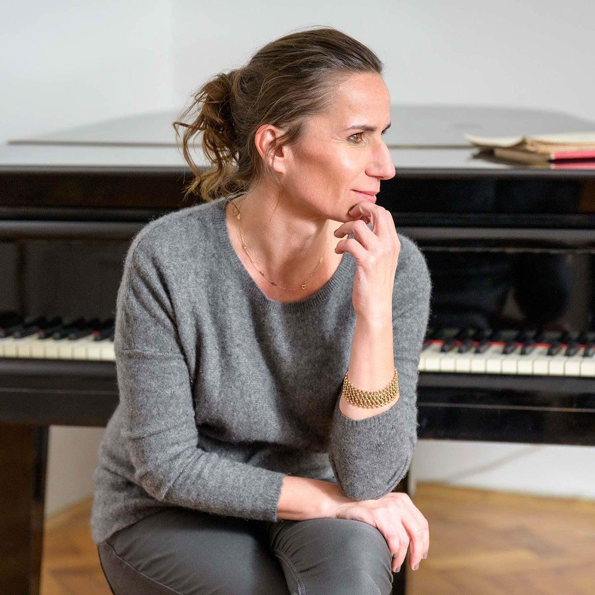 Seitliches Porträt einer Frau mit Klavier im Hintergrund